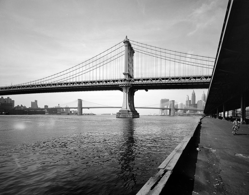 Edmund V. Gillon, photographer. Looking south on South Street to the Manhattan and Brooklyn Bridges and the Lower Manhattan skyline, c. 1977. Image and data provided by Museum of the City of New York.