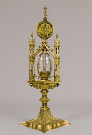 A gilded reliquary with a central clear crystal ovoid vessel.