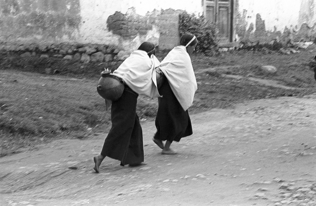 Frank Cancian. Women carrying water in the street (Another Place). 1971. Black-and-white photograph. © 2001 Frank Cancian. Image and data provided by University of California Irvine Libraries.