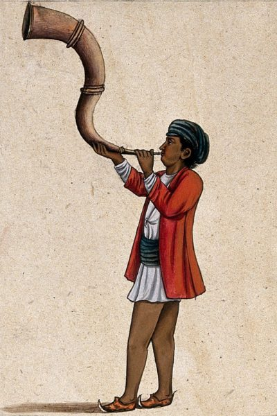 An Indian musician playing a long, inverted 's' shaped trumpet.